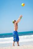 打在海滩的可爱的年轻人排球 免版税库存图片