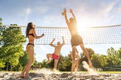 打在海滩的小组年轻朋友排球 免版税库存照片