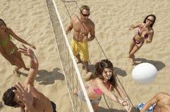 打在海滩的朋友排球 免版税库存图片