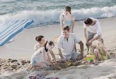 打在海滩的笑的家庭比赛周末 免版税库存图片
