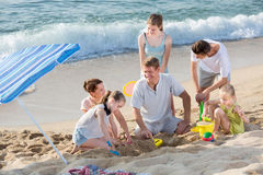打在海滩的笑的家庭比赛周末 库存图片