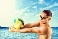 打在海滩的年轻人排球 免版税库存图片
