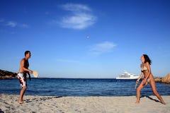 打在海滩的年轻夫妇网球。 免版税库存图片