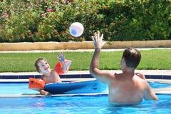 打在游泳池的父亲和儿子球 免版税图库摄影