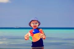 打在热带海滩的孩子球 免版税库存图片