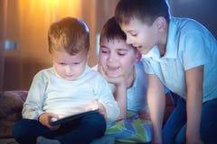 打在片剂个人计算机的孩子比赛 有片剂计算机的三个小男孩 免版税库存照片