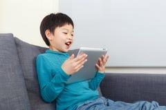 打在片剂的亚洲小男孩比赛 免版税库存照片