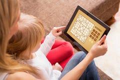 打在片剂计算机上的母亲和女儿比赛 免版税库存照片