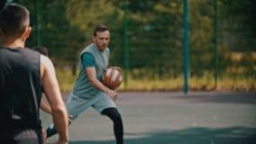 打在的年轻人篮球运动场与朋友-滴下,避免他的对手 股票视频