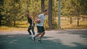 打在的年轻人篮球运动场与朋友-滴下,避免他的对手-击中目标 股票视频