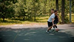 打在的年轻人篮球运动场与朋友-滴下,避免他的对手-投掷球  影视素材