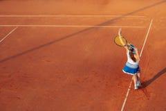 打在红土网球场的妇女网球,与运动的成套装备和健康生活方式 图库摄影