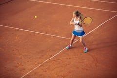 打在红土网球场的妇女网球,与运动的成套装备和健康生活方式 免版税库存照片