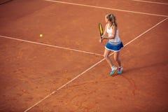 打在红土网球场的妇女网球,与运动的成套装备和健康生活方式 库存照片