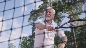 打在网球场的画象快乐的愉快的微笑的成熟人网球 老人投掷与球拍的球 影视素材