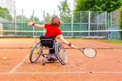 打在网球场的轮椅的残疾少妇网球 免版税库存照片