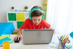 打在膝上型计算机的耳机的男孩电子游戏 图库摄影