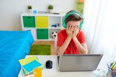 打在膝上型计算机的耳机的男孩电子游戏 库存图片