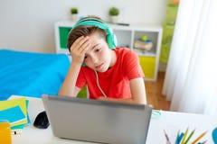 打在膝上型计算机的耳机的男孩电子游戏 免版税库存图片