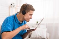 打在膝上型计算机的被集中的青少年的男孩电子游戏 库存图片