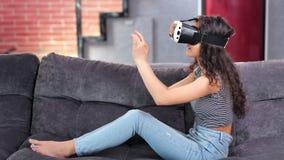 打在虚拟现实模拟器玻璃的赤足微笑的年轻女人比赛在长沙发 股票视频