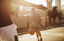打在街道上的人篮球 免版税库存图片