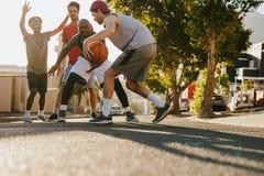 打在街道上的人篮球 库存图片