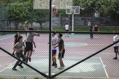 打在街道大厅的孩子前面射击篮球 库存图片
