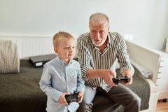 打在计算机上的祖父和孙子电子游戏有控制杆的 免版税库存照片