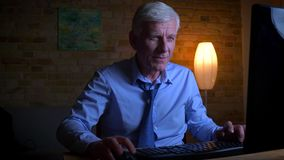 打在计算机上的老白种人商人特写镜头画象电子游戏户内在与光的公寓 影视素材
