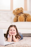 打在计算机上的逗人喜爱的女孩比赛 库存图片