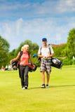 打在路线的年轻嬉戏夫妇高尔夫球 免版税库存图片