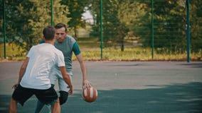 打在运动场的年轻人篮球与朋友,滴下 影视素材