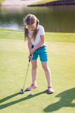 打在领域的逗人喜爱的小女孩高尔夫球 免版税图库摄影