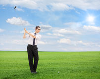 打在领域的年轻人高尔夫球 图库摄影