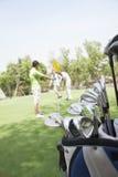 打在高尔夫球场的三个朋友高尔夫球,在小型运车的焦点 库存照片