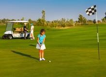 打在高尔夫球场的嬉戏家庭高尔夫球 免版税库存照片