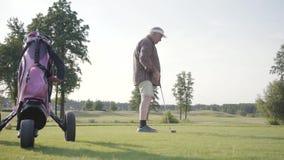 打在高尔夫球领域的成熟人高尔夫球 使用高尔夫俱乐部,老人击中了球 打比赛的老绅士户外 股票视频