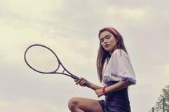 打在绿色法院的女孩网球 免版税库存照片