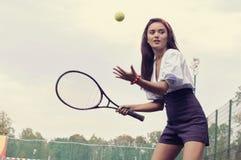 打在绿色法院的女孩网球 库存照片