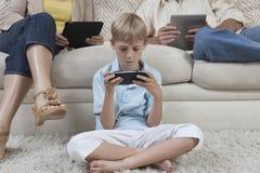 打在PSP的小男孩比赛 免版税库存照片