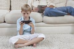 打在PSP的男孩比赛 免版税库存照片
