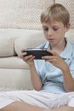 打在PSP的男孩比赛 免版税图库摄影