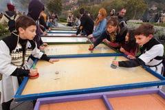 打在Tbilisoba节日儿童操场的传统服装的男孩有些比赛  免版税图库摄影