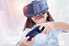 打在VR耳机的微笑的女孩电子游戏 图库摄影
