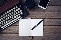 打字机顶上的看法由一次性杯子和书的 免版税库存照片
