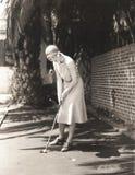 打小小高尔夫球的妇女 库存照片