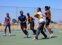 打少女玩的篮球赛的不同的孩子在学校 免版税库存图片