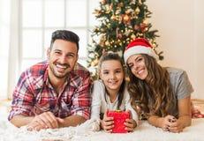 打开一个不可思议的礼物的逗人喜爱的女孩在与她的家庭的一圣诞节早晨 免版税库存照片