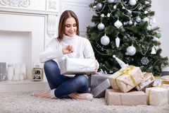 打开一个圣诞节礼物的少妇在一圣诞节早晨 库存图片